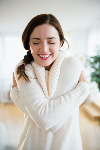 Woman giving herself a hug, smiling
